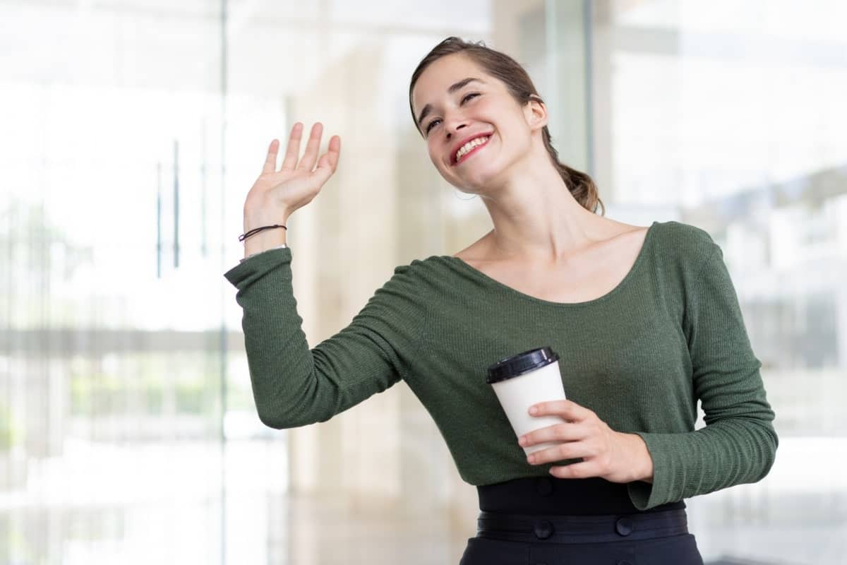 woman waving with coffee cup