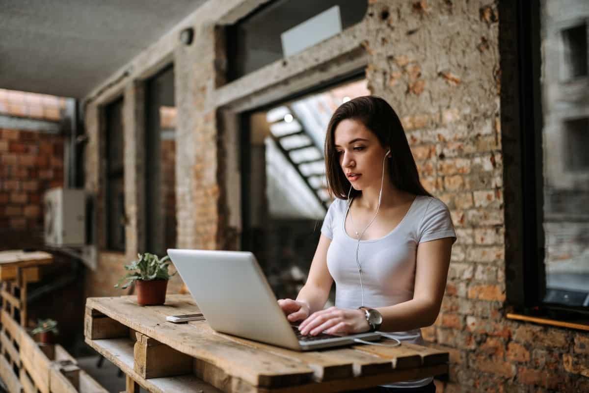 Blogger donna utilizzando laptop e indossando gli auricolari
